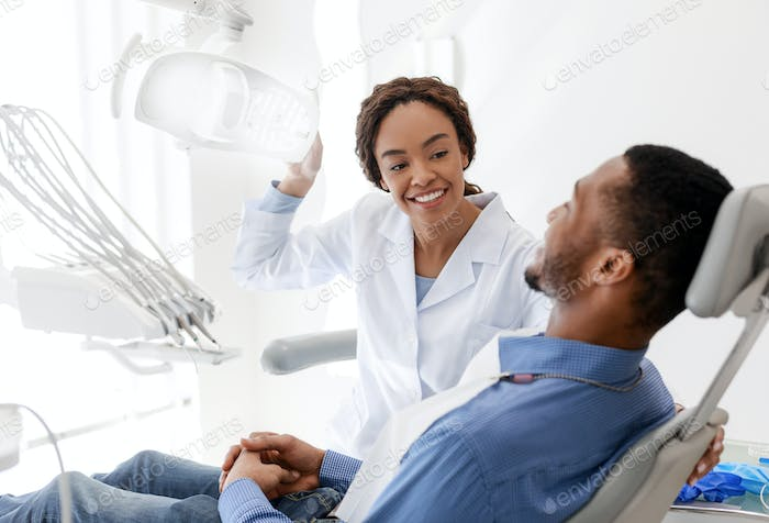 Female dentist turning on lamp before treatment