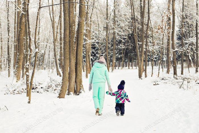 glückliche Mutter und Baby-Mädchen auf dem Spaziergang im Winter verschneiten Wald