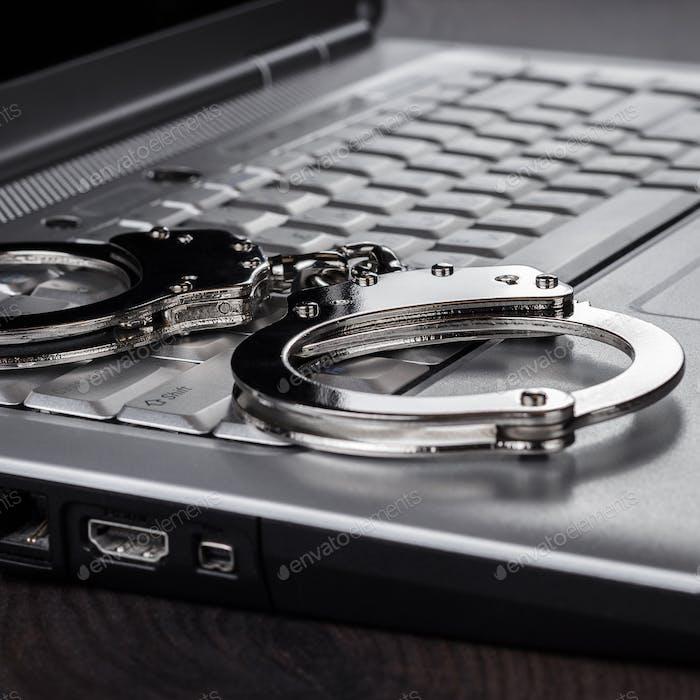 Handschellen auf Laptop Cyber Crime Konzept