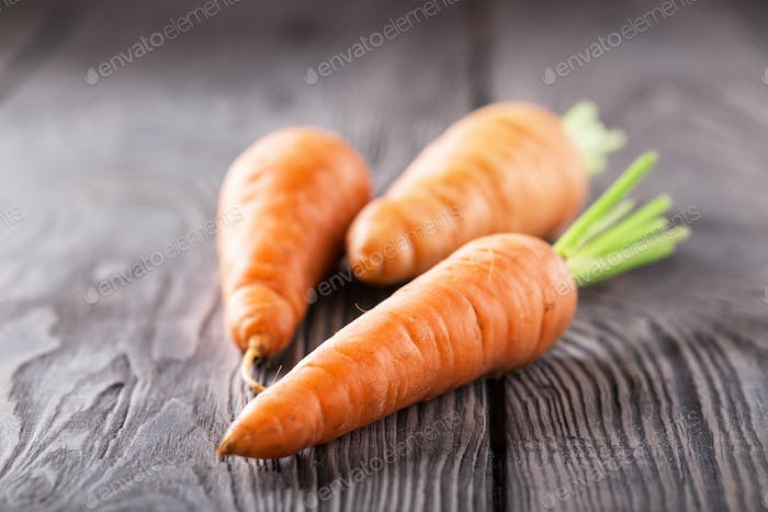Three bright juicy carrots with green cuttings