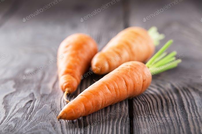 Drei helle saftige Karotten mit grünen Stecklingen