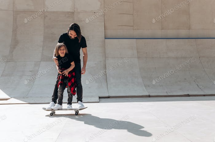 Father and his little son dressed in the casual clothes stand together on the one skateboard in a