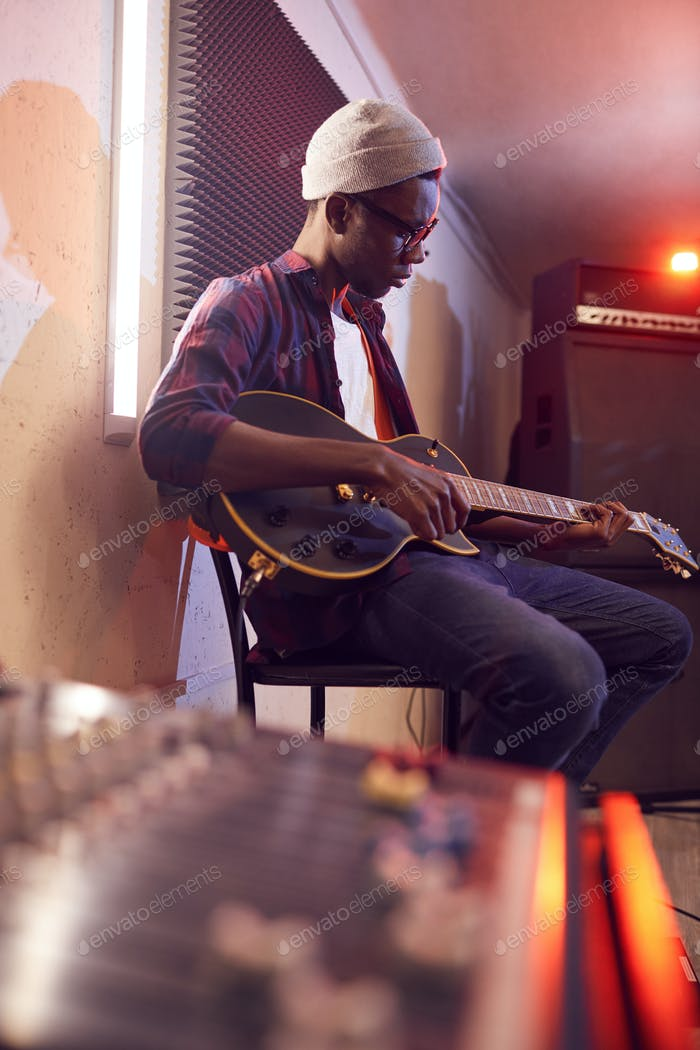 Young African Man Playing Guitar in Studio