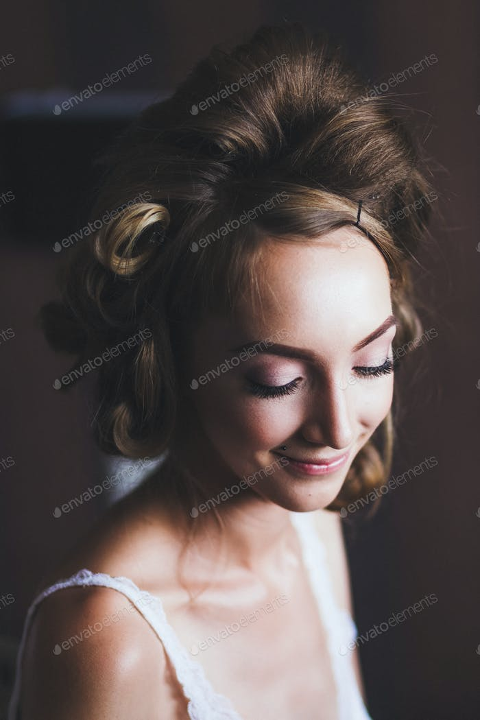 Bride makes hairstyle before the wedding. Long hair with curls and hair curlers