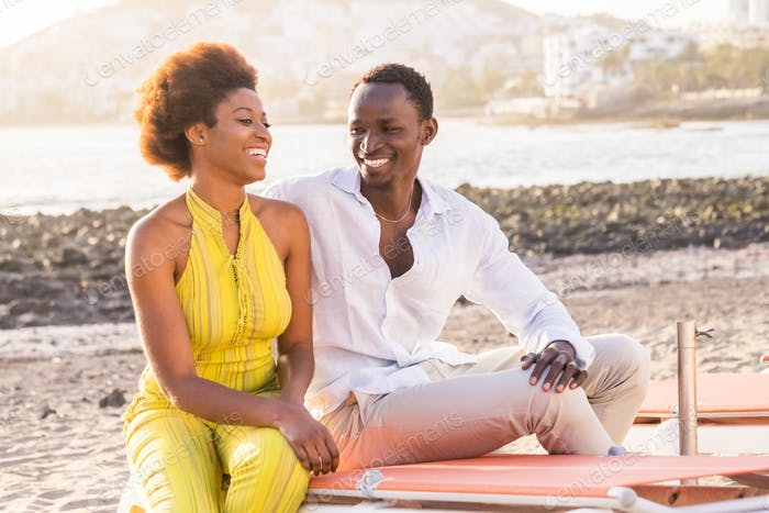 happy black race african couple at the beach smiling and enjoying the leisure activity together