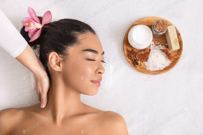 Relaxed asian woman enjoying neck massage with natural ingredients cosmetics at spa