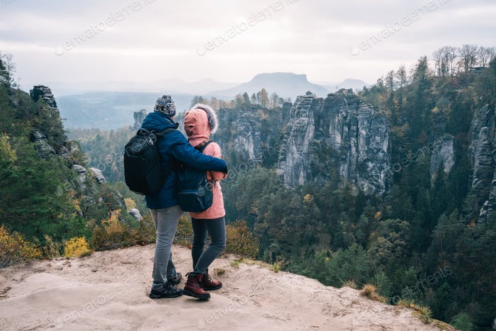 Young couple in outdoor clothing with backpacks standing on plateau enjoying view of mountain ridge