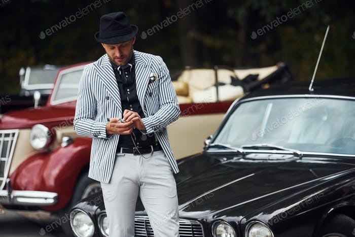 Man in formal clothes and black hat stands near retro automobiles