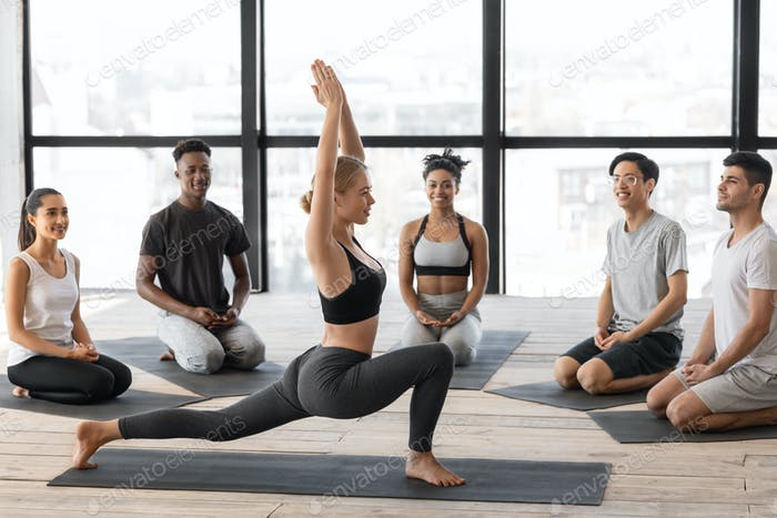 Professional Yoga Instructor Woman Showing Different AsanasTo Group Lesson Members In Studio
