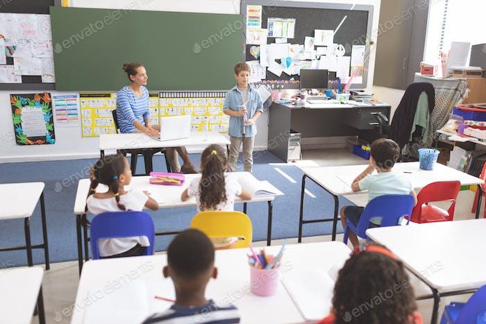 Schuljunge erklärt über Windmühle vor seinen Klassenkameraden