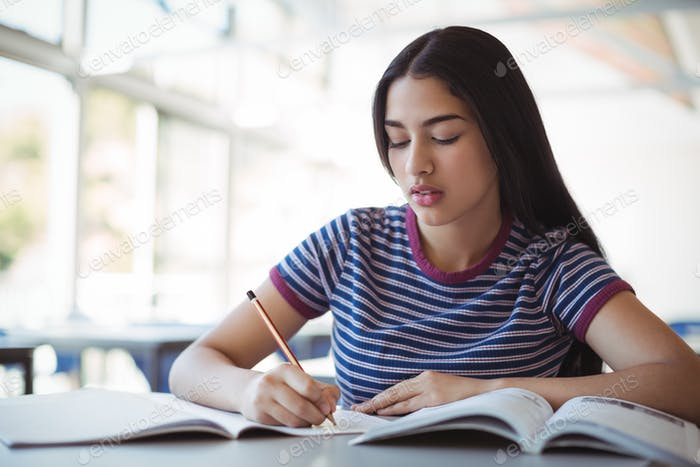 Attentive schoolgirl doing homework in classroom