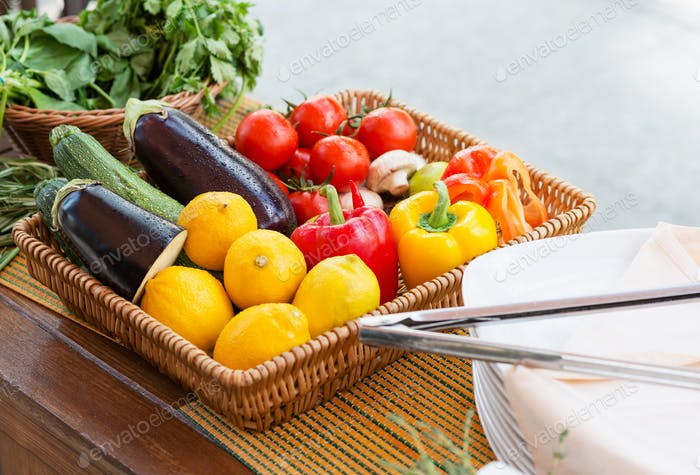 ingredients for cooks mix of fresh vegetables for roasting in a wicker basket on the table