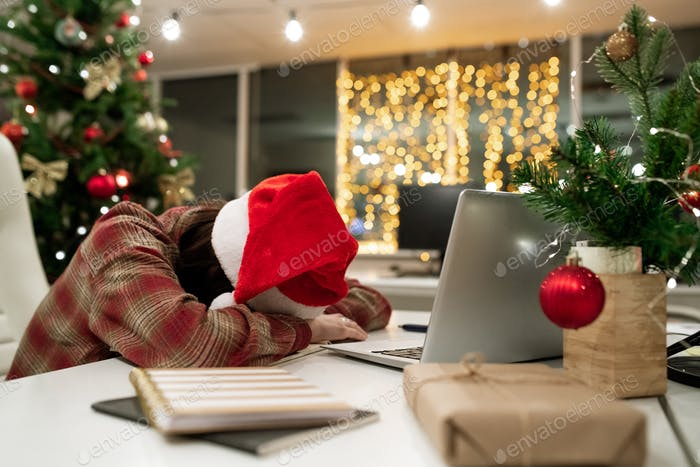 Exhausted young businesswoman in Santa cap sleeping by desk in front of laptop