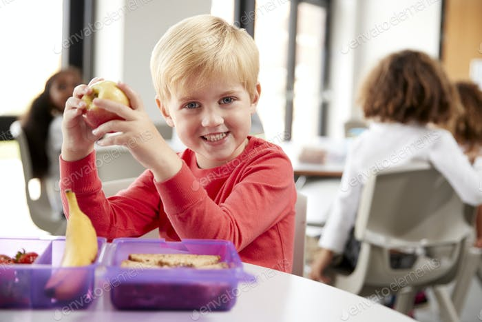 Young white schoolboy sitting at a table smiling and holding an apple in a kindergarten classroom