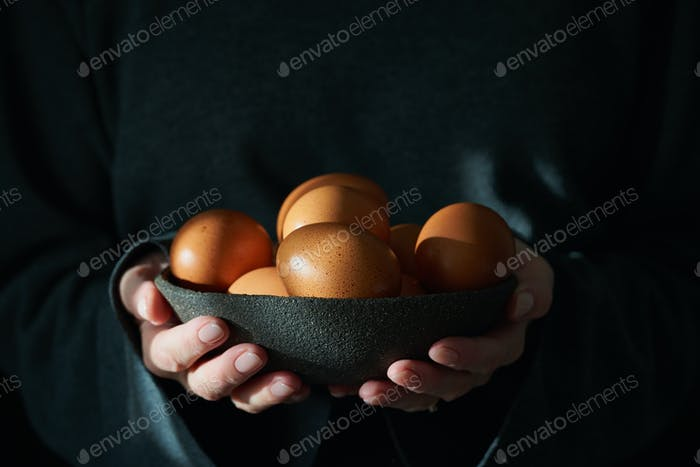 Unusual Easter on dark background. Bowl of brown eggs with hands.