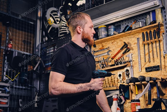 Red head bearded bicycle mechanic holds screwdriver.