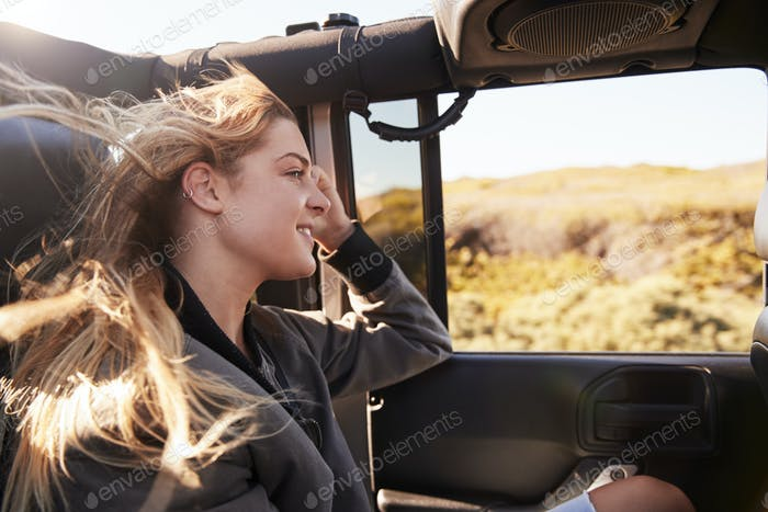 Young white woman admiring the scenery from an open car