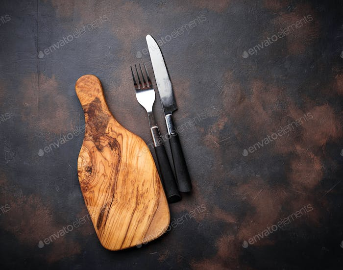 Wooden cutting board, fork and knife