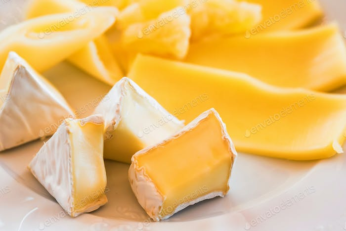 Sliced white mold cheese on plate close