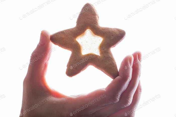 Hand holding star cookie with syrup.