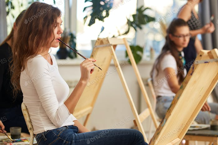 Charming girl with brown curly hair dressed in white blouse creates a picture at the easel holding