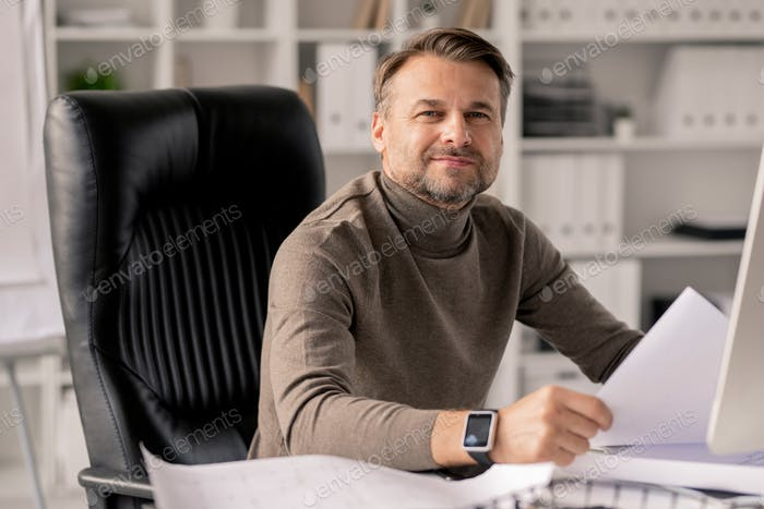 Successful mature engineer with papers looking at you while in armchair by desk