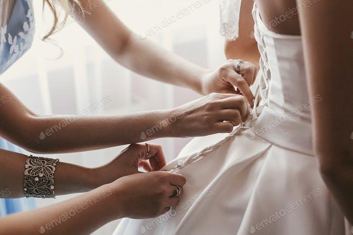 Brautjungfern und Mutter helfen wunderschönen Braut immer bereit für die Hochzeit