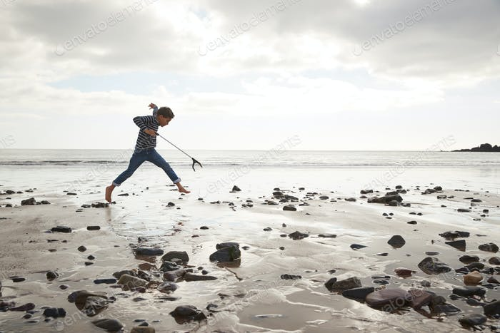 Young Boy Collecting Litter On Winter Beach Clean Up