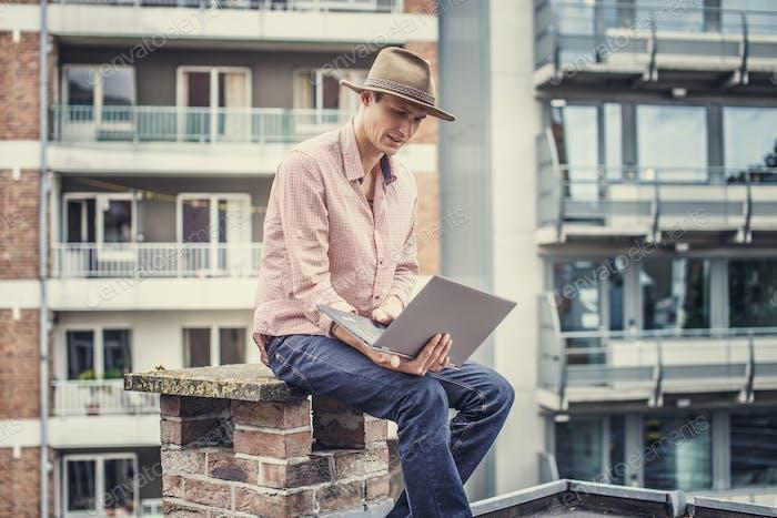 Mann mit Hut mit Laptop.