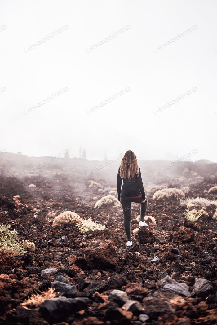 Young woman contemplating the fog on her way to Teide top in Tenerife, Spain