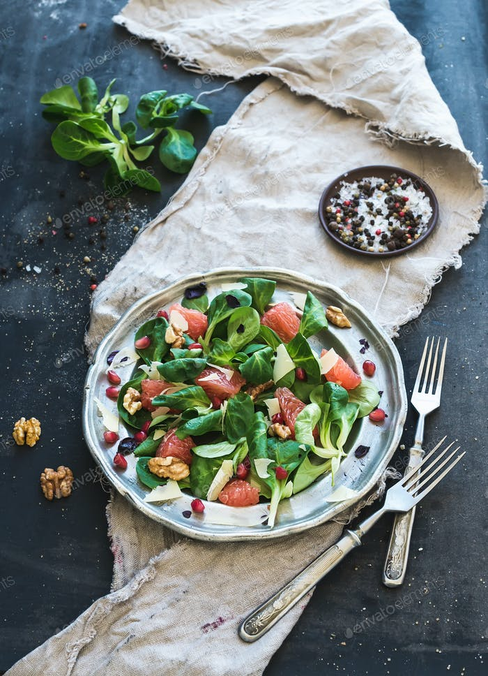 Spring salad with lamb's lettuce, grapefruit, garnet, walnuts in vintage metal plate