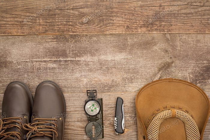 top view of boots, compass, jackknife and hat on wooden table