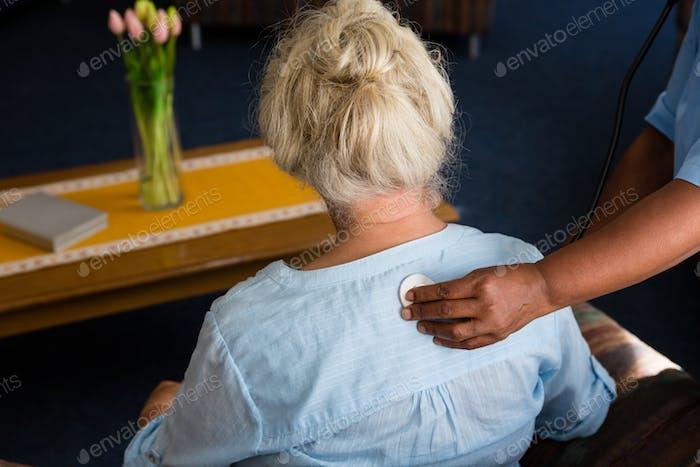 Hand of nurse examining patient in retirement home