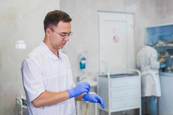 closeup of a caucasian doctor man, wearing a white coat, putting on a pair of blue surgical gloves