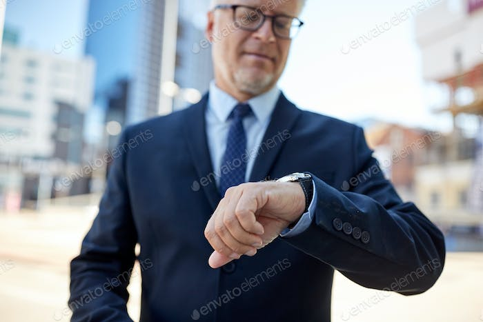 senior businessman with wristwatch on city street