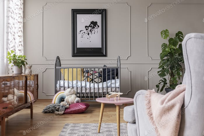 Map in black frame above grey crib full of colorful pillows and