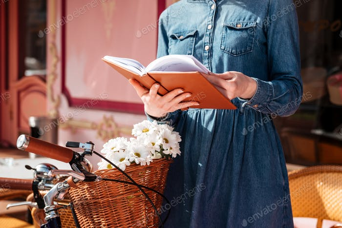 Woman with bicycle reading a book outdoors