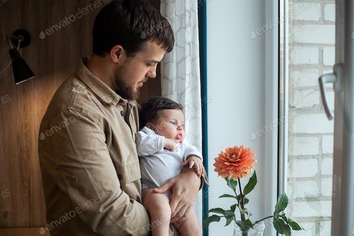 Junger Vater hält Baby sanft zu Hause. Konzept der Familie, Kindheit und Vaterschaft.