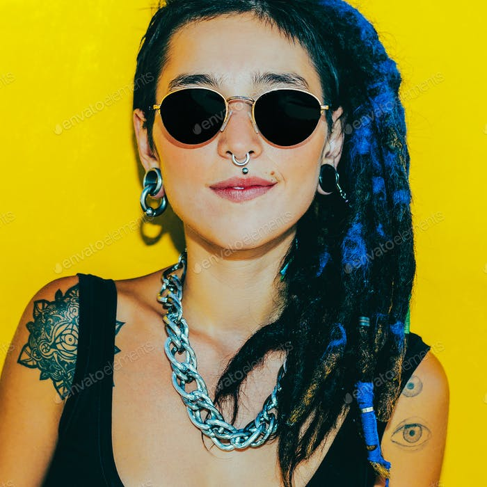 Fashion pretty cool girl with dreadlocks and piercings over colo