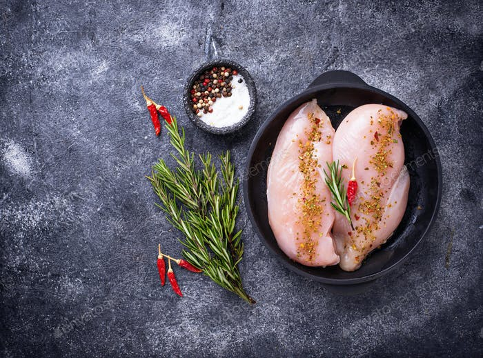 Raw chicken fillet in cast iron pan