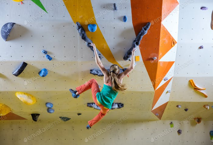 Young woman falling down while bouldering in climbing gym