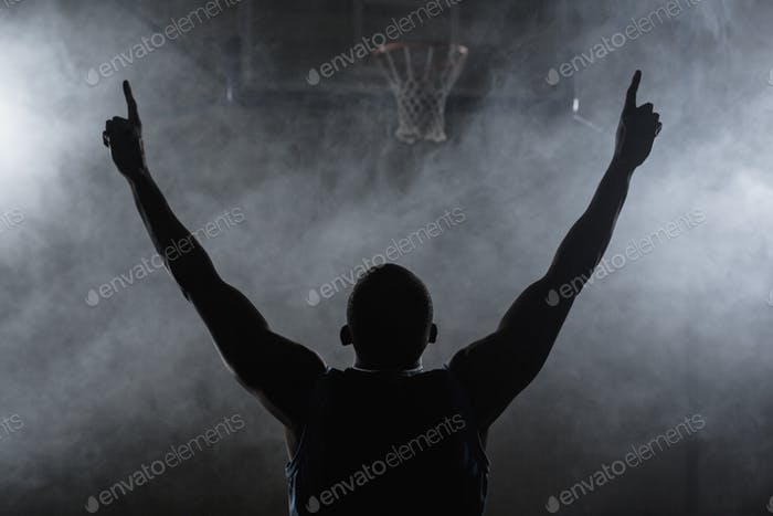 Rear view of a basketball player with his arms in the air