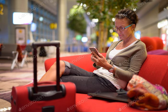 Mature beautiful tourist woman using phone at the lounge indoors