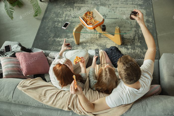 Family spending nice time together at home, looks happy and cheerful, eating pizza. Top view