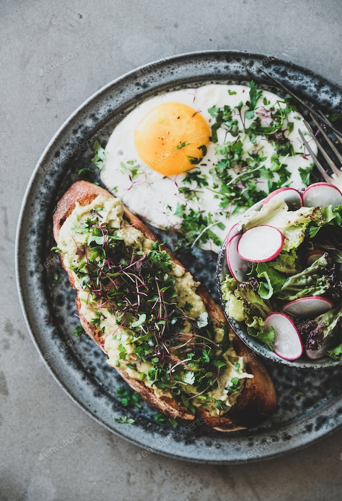 Avocado toast on bread, fried egg and salad with radish