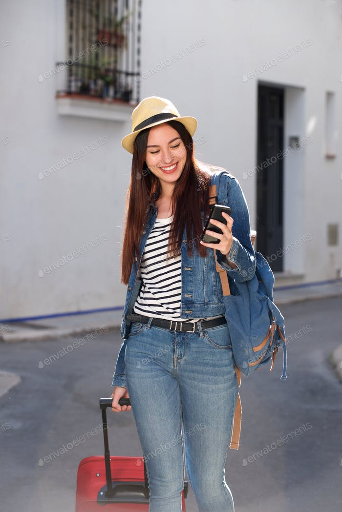 Smiling woman walking with luggage and holding cellphone outside