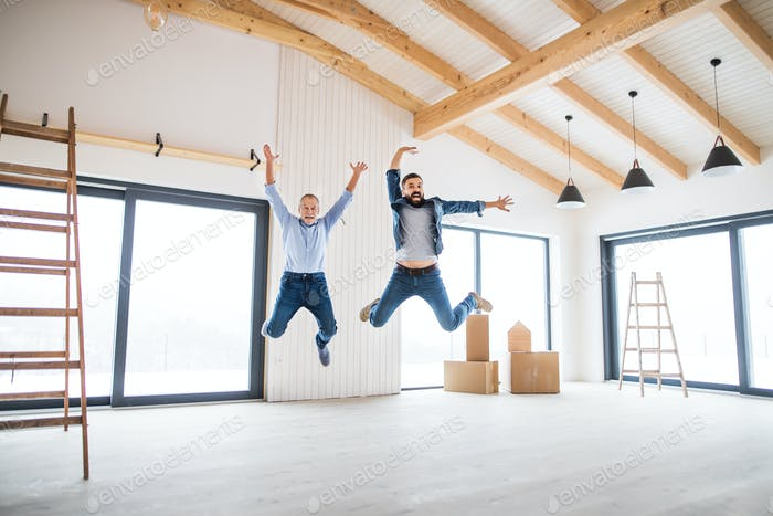 A mature man jumping with his senior father in new house, a new home concept.