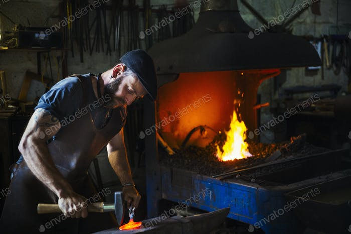 A blacksmith strikes a pieces of red hot metal on an anvil with a hammer in a workshop.