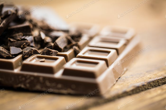 Close up view of dark and milk chocolate on a wooden table