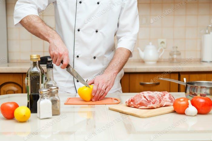 Nahaufnahme auf den Händen schneiden gelben Pfeffer auf professionelle Küche.
